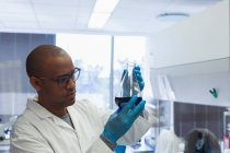Scientist checking a solution in conical flask at lab — Stock Photo
