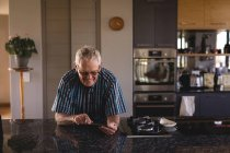 Senior man using digital tablet in kitchen at home — Stock Photo