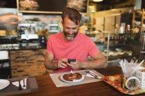 Homme souriant, à l'aide de téléphone portable en boulangerie pà ¢ tisserie — Photo de stock