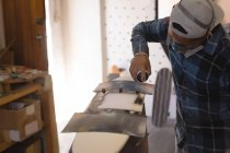 Man spray painting skateboard in workshop — Stock Photo