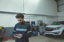 Mecánico mediante teléfono móvil mientras se repara el coche en el garaje - foto de stock