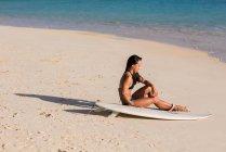 Жінка розслаблювальним з дощок для серфінгу в Біч у сонячний день — стокове фото