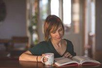 Belle livre de lecture femme tout en prenant un café à la maison — Photo de stock
