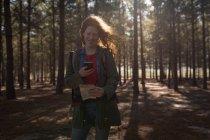 Mulher sorridente usando telefone celular na floresta — Fotografia de Stock