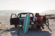 Couple taking selfie with mobile phone in a pickup truck at beach — Stock Photo