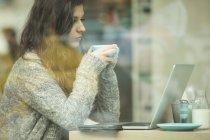 Молодая женщина пьет кофе во время использования ноутбука в кафе — стоковое фото