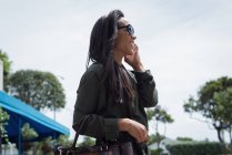 Smiling woman in sunglasses talking on mobile phone — Stock Photo