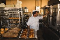 Maduro masculino baker trabaja en la tienda del panadero - foto de stock