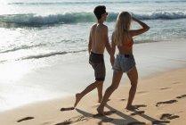 Пара, ходить вместе рука об руку на пляже — стоковое фото