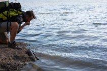 Вид сбоку мужчин туристы питьевой воды из реки — стоковое фото