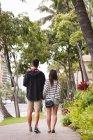Задній вид пари разом ходіння по тротуару в місті — стокове фото