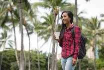 Sonriente hermosa mujer sosteniendo la taza de café en el parque - foto de stock