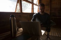 Thoughtful man using laptop at log cabin — Stock Photo