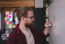 Männliche Führungskräfte schreiben auf Whiteboard im Büro — Stockfoto