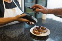 Клієнт робить оплату за допомогою мобільного телефону в магазині Бейкер — стокове фото