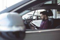 Salesman reading brochure inside the car at showroom — Stock Photo