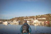 Вид сзади мужчин туристы стоя с рюкзаком на гавань — стоковое фото