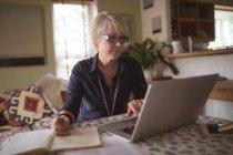 Зрілі жінки, використовуючи ноутбук під час запису в щоденнику вдома — стокове фото
