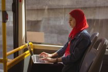 Beautiful hijab woman using laptop while travelling in bus — Stock Photo