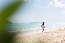 Женщина, ходить в одиночку на пляже в Солнечный день — стоковое фото