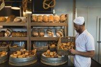 Padeiro masculino segurando cesta de croissants na padaria — Fotografia de Stock