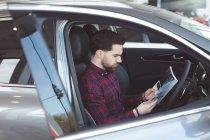Vendedor leyendo el folleto dentro del coche en el salón de muestras - foto de stock