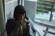 Jeune femme prenant un café à la maison — Photo de stock
