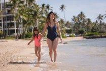 Sonriente de la madre y su hija tomados de la mano y caminar en la playa - foto de stock