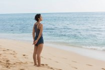 Beautiful woman standing with eyes closed in the beach — Stock Photo