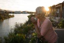 Femme âgée prenant un café dans le balcon à la maison — Photo de stock