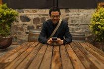 Uomo d'affari sorridente utilizzando il telefono cellulare nel caffè marciapiede — Foto stock