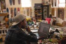 Уважна людина, використовуючи ноутбук у майстерні — стокове фото