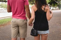 Rear view of couple walking together on sidewalk in the city — Stock Photo