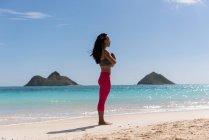 Женщина, выполняя йоги на пляже в Солнечный день — стоковое фото