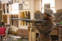 Человек осматривает скейтборд в мастерской — стоковое фото