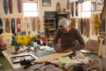 Homme faisant skateboard en atelier — Photo de stock