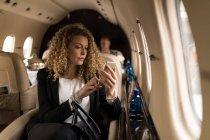 Schöne geschäftsfrau mit Handy im Privatjet — Stockfoto