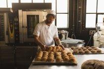 Hombre panadero arreglo alimentos dulces cocidos al horno en la panadería - foto de stock