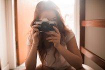 Donna facendo clic su foto con la fotocamera a casa — Foto stock