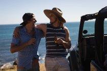 Amigos varones tomando cerveza en la playa en un día soleado - foto de stock