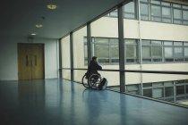 Vista traseira do homem deficiente em cadeira de rodas olhando para fora do painel de vidro — Fotografia de Stock