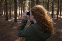 Женщина смотрит через бинокль в лесу в солнечный день — стоковое фото