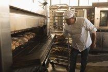 Maduro hombre panadero con owen en la panadería de la hornada - foto de stock