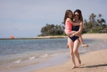 Madre e hija caminando juntos en la playa en un día soleado - foto de stock