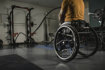 Handicapped man on wheelchair exercising with battle ropes in gym — Stock Photo