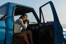 Mujer durmiendo en una camioneta en la playa - foto de stock