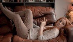 Жінка, що використання мобільного телефону у вітальні на дому — стокове фото