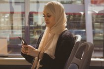 Beautiful hijab woman using mobile phone while travelling in the bus — Stock Photo