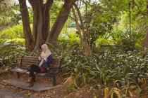 Hijab woman sitting on bench and using mobile phone at garden — Stock Photo