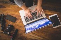 Vlogger femenino usando portátil en la mesa en casa - foto de stock